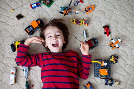 Klein kind spelen met veel kleurrijke plastic speelgoed indoor, het bouwen van verschillende auto's en objecten