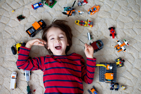 plastic toys: Little child playing with lots of colorful plastic toys indoor, building different cars and objects Stock Photo