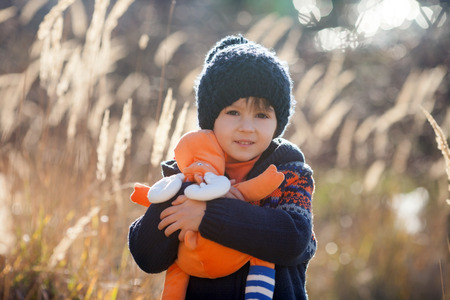 single story: Cute little caucasian child, boy, holding fluffy toy, hugging it, in the park, on sunny winter day