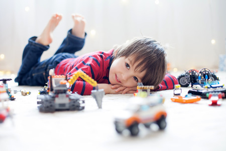 Little child playing with lots of colorful plastic toys indoor, building different cars and objects Stockfoto