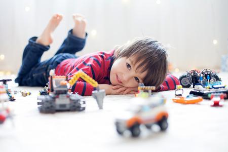 Pequeño niño que juega con un montón de juguetes de plástico de colores interiores, la construcción de diferentes vehículos y objetos