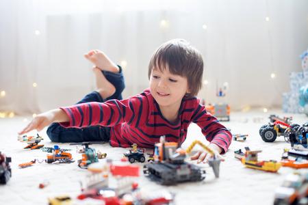 다른 자동차와 개체를 실내 다채로운 플라스틱 장난감을 많이 가지고 노는 건물 작은 아이