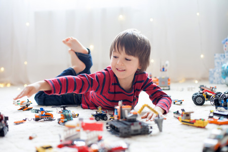 Little child playing with lots of colorful plastic toys indoor, building different cars and objects Foto de archivo