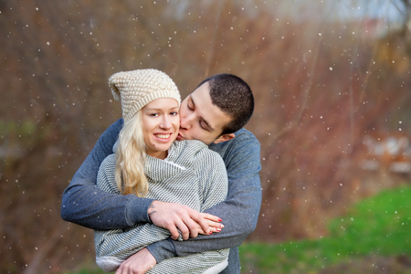 young boy smiling: Young attractive couple in love, teenagers having fun outdoors, kissing and hugging Stock Photo