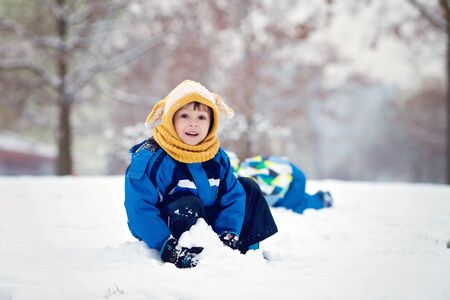 hermanos jugando: Two boys, brothers, playing in the snow with snowballs, wintertime