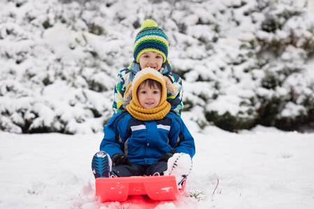 boy smiling: Two kids, boy brothers, sliding with bob in the snow, wintertime, happiness concept Stock Photo
