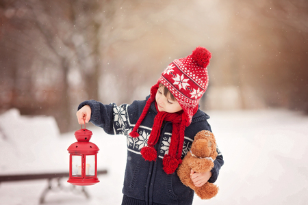 beautiful boy: Cute little caucasian boy with teddy bear and red lantern, playing in the winter park, snowy day Stock Photo