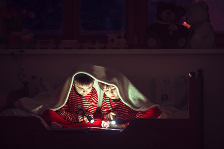 Two sweet boys, reading a book in bed after bedtime, using flashlights, winter night