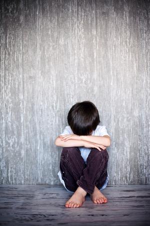 asustado: Chico joven, sentado en el suelo con su oso de peluche, la tristeza en sus ojos