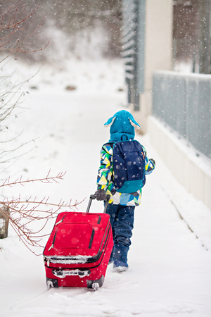 ski walking: Cute little boy with backpack and red suitcase, going on a ski holiday, walking in the park
