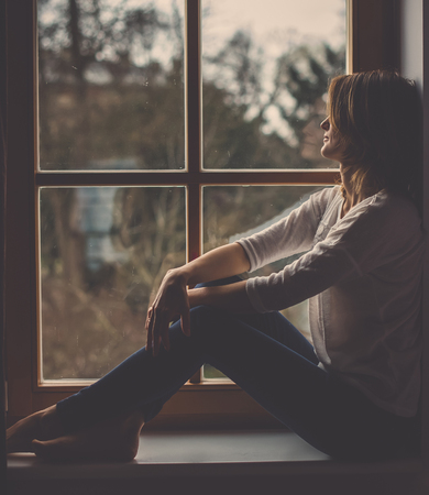 Young attractive woman, sitting on a window, looking outside, lonely mood Stock Photo