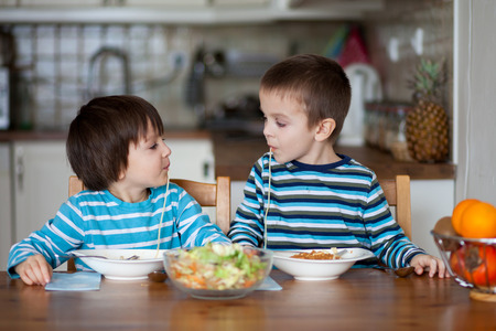 mealtime: Two sweet children, boy brothers, having for lunch spaghetti at home, enjoying tasty food