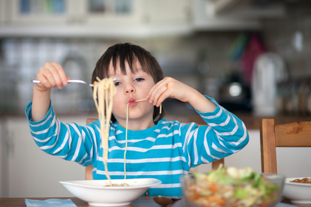 lunchtime: Cute little boy, eating spaghetti at home for lunchtime, tasty food