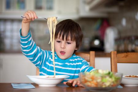 Schattige kleine jongen, het eten van spaghetti thuis voor de lunch, lekker eten
