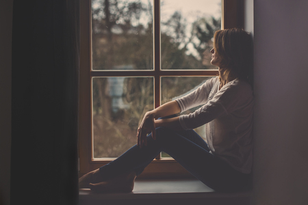 Young attractive woman, sitting on a window, looking outside, lonely mood Foto de archivo