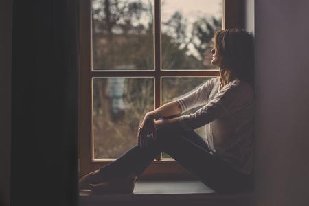 Młoda atrakcyjna kobieta, siedzi na oknie, patrząc na zewnątrz, samotny nastrój