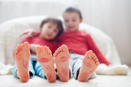 Kleine kinderen voeten, bedekt met prints van kussen, kinderen spelen op tablet