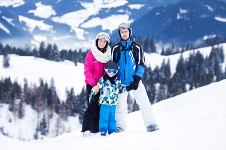 boy lady: Young happy family with one child, skiing in the mountains, wintertime