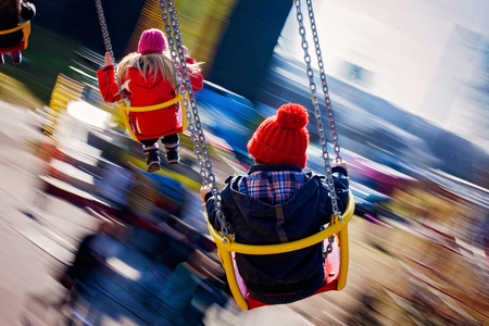chain swing ride: Kids, having fun on a swing chain carousel ride, motion blur