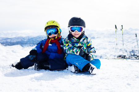 cool kids: Two young children, siblings brothers, skiing in Austrian mountains on a sunny day, wintertime, enjoying sports