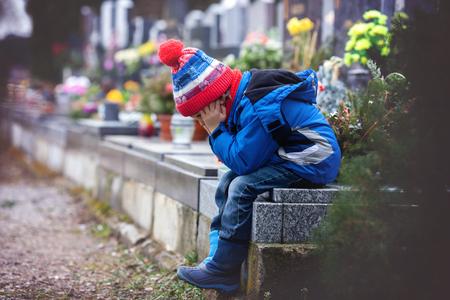 Sad jongetje, zittend op een graf in een begraafplaats, verdrietig en huilen