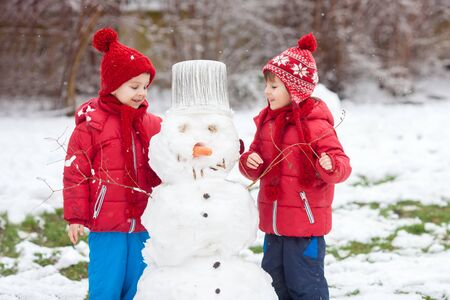 Happy beautiful children, brothers, building snowman in garden, winter time