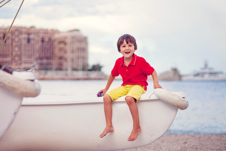 toddler boy: Boy, sitting on a boat, playing on the beach in the evening after rain with toys, summertime Stock Photo