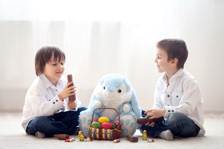 back light: Two adorable little children, boy brothers, having fun eating chocolate bunnies and playing with eggs at home, back light Stock Photo