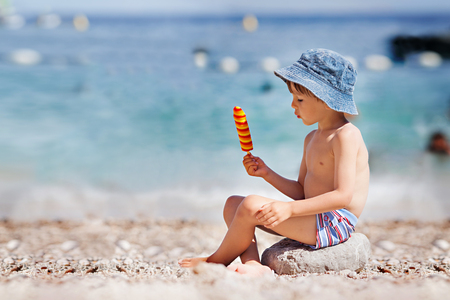 Sweet little child, boy, eating ice cream on the beach, summertime 版權商用圖片