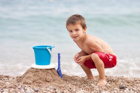 beach toys: Cute little preschooler boy, playing in the sand on the beach with beach toys, Monaco beach, Europe Stock Photo