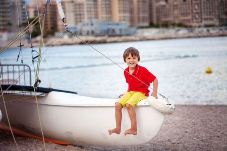 beach rain: Boy, sitting on a boat, playing on the beach in the evening after rain with toys, summertime Stock Photo