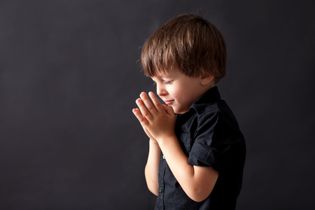 implore: Little boy praying, child praying, isolated black background Stock Photo