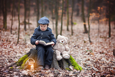 fear child: Cute little child, preschool boy, sitting on a tree trunk with his teddy bear, reading a book Stock Photo