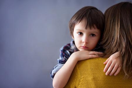 Droevig weinig kind, jongen, knuffelen zijn moeder thuis, geïsoleerde afbeelding, kopieer ruimte. familie concept