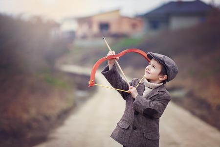 arco y flecha: Adorable ni�o de edad preescolar, tirar con el arco y la flecha en la diana en el aire libre, la primavera al aire libre Foto de archivo