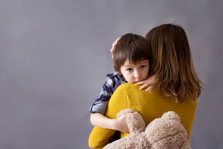 Droevig weinig kind, jongen, knuffelen zijn moeder thuis, geïsoleerde afbeelding, kopieer ruimte. familie concept Stockfoto