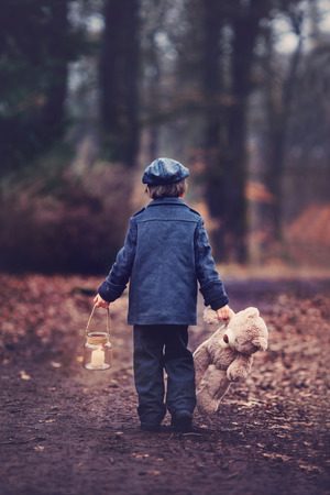 Cute little child, preschool boy, holding lantern and teddy bear, walking in a dark forest Фото со стока