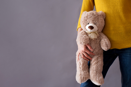 protection concept: Young girl, holding sweet fluffy teddy bear, isolated image Stock Photo