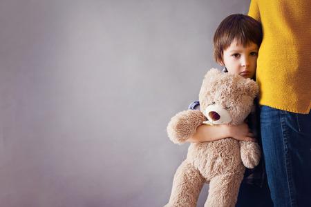 Trauriges kleines Kind, Junge, seine Mutter zu Hause umarmend, lokalisierte Bild, Kopienraum. Familienkonzept Standard-Bild