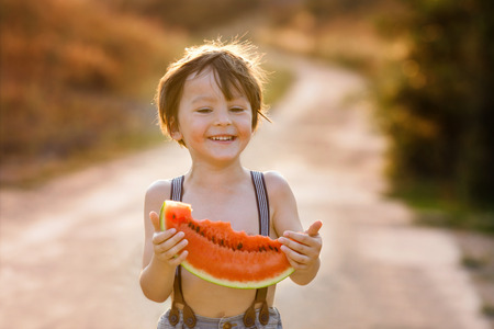 hot day: Beautiful little happy child, boy, eating big slice of watermelon, summertime outdoor on sunset