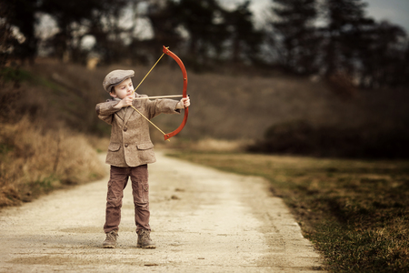 사랑스러운 작은 유치원 소년, 야외에서 봄 날 야외에서 활과 화살 대상에서 촬영
