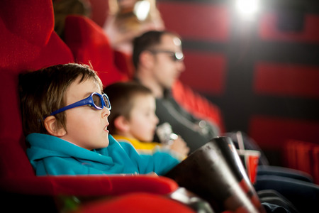 father with child: Father and two children, boys, watching cartoon movie in the cinema on 3D Stock Photo