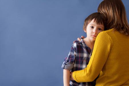 niños tristes: Sad pequeño niño, muchacho, que abraza a su madre en casa, aislada, copia espacio. concepto de familia
