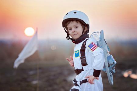 우주 비행사처럼 옷을 입고 사랑스러운 작은 소년, 로켓, 플래그와 함께 공원에서 재생 우주 비행사가되기에 대한 꿈 스톡 콘텐츠