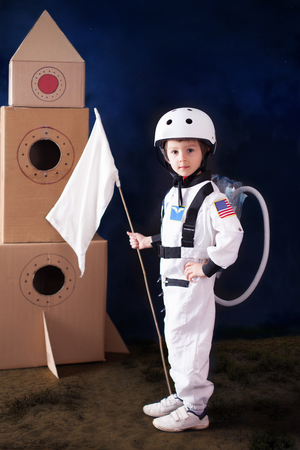 Beautiful preschool boy, dressed as astronaut, with flag and carton rocket, proudly standing
