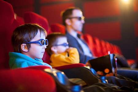 chair cartoon: Father and two children, boys, watching cartoon movie in the cinema on 3D Stock Photo
