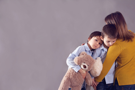 Sad little children, boys, hugging their mother at home, isolated image, copy space. Family concept