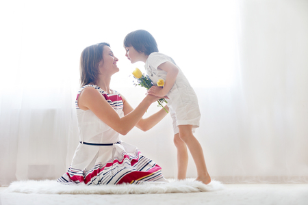 hugs and kisses: Mother and her child, embracing with tenderness and care, child  giving mother flowers. Mother day concept, happiness and love Stock Photo