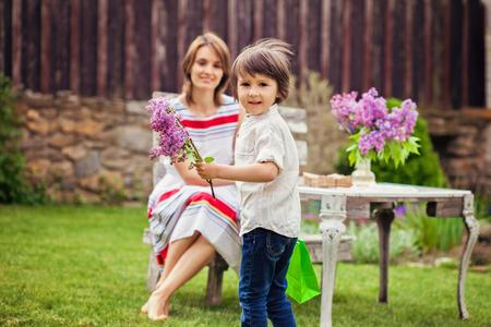 familias jovenes: Hermosa mamá, tomando un café en un patio trasero, joven niño lindo que da su presente y flores para su cumpleaños. Madre concepto de día, amor, felicidad, ambiente acogedor