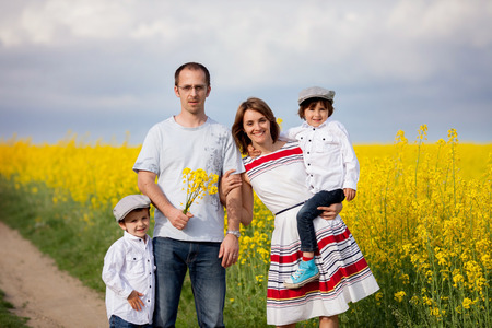 adult rape: Family of four, mother, father and two boys,  in a oilseed rape field, laughing, smiling, hugging, giving a kiss, holding flowers